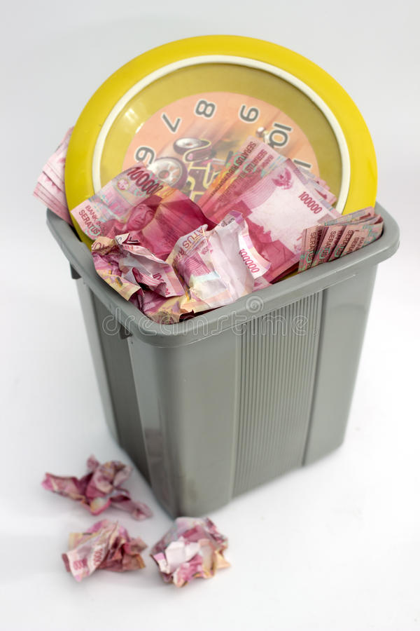 Wasting time and money. Indonesian money rupiah and yellow clock on a bin stock photography