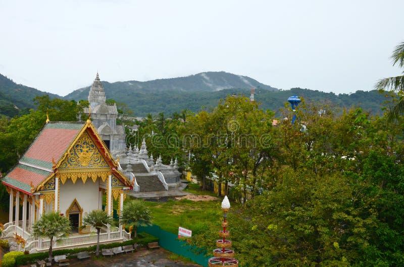 Wat查龙寺庙,普吉岛,泰国 在寺庙塔和大厦的顶视图在绿色山背景的  库存图片