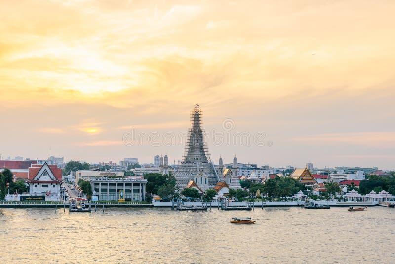 Wat Arun The Temple rinnovato dell'alba con le barche che si sposta per il fiume di Chaophraya nella sera a Bangkok, Tailandia immagine stock libera da diritti