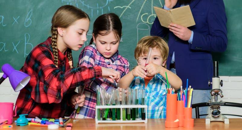 Wat een probleem schijnt te zijn jonge geitjes in laboratoriumlaag het leren chemie in schoollaboratorium Chemielaboratorium Gelu stock fotografie
