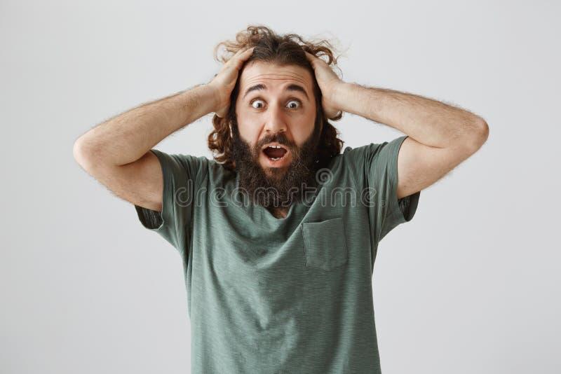 Wat gedaan u, het hebben zijn vreselijk Geschokte en gefrustreerde oostelijke mens met handen op hoofd houden en baard die, die h stock foto's
