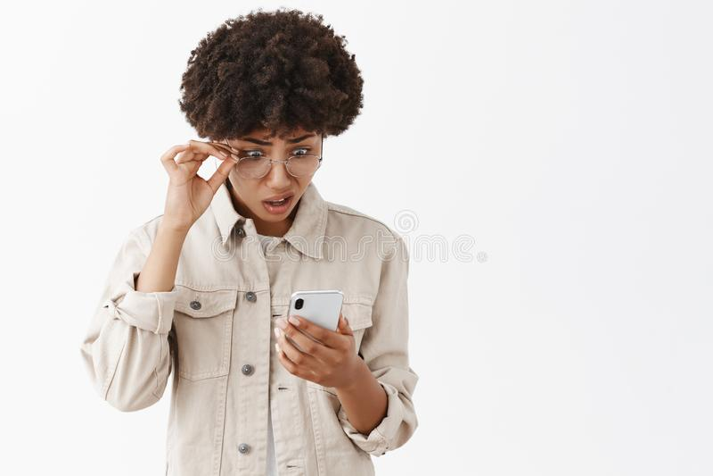 Wat Het portret van verwarde en gevraagde intense Afrikaanse Amerikaan kan niet geloven in onzin die zij heeft gelezen via stock afbeelding