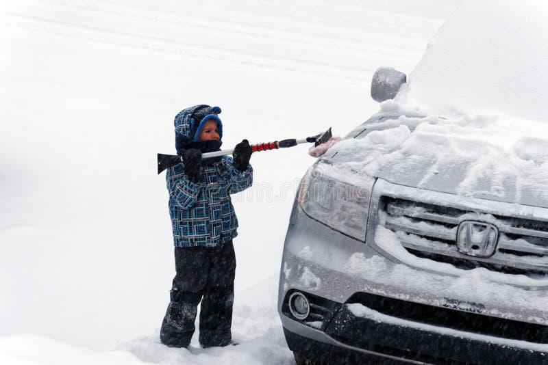 Wat jongen het borstelen sneeuw van een auto stock foto