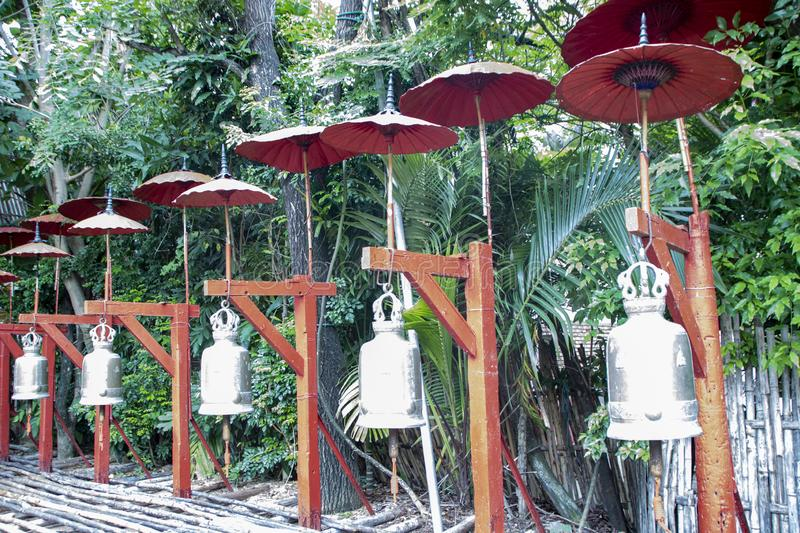 Wat Pan Tao. Bells and red paper umbrellas in the garden of Wat Pan Tao, beautiful old wooden teak temple in Chiang Mai, Thailand royalty free stock images