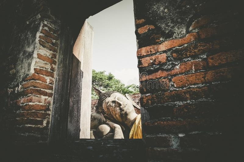 Wat Phutthaisawan Reclining Buddha in Ayutthaya Thailand. UNESCO heritage destination . view through window ruins of acient temple. Travel and exploration stock photo