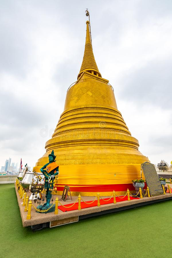 Wat Saket temple with golden stupa and angel statue. Symbol of buddhism in Bangkok city, Thailand. Majestic and religion symbol of. Thai culture. Cloudy weather royalty free stock images