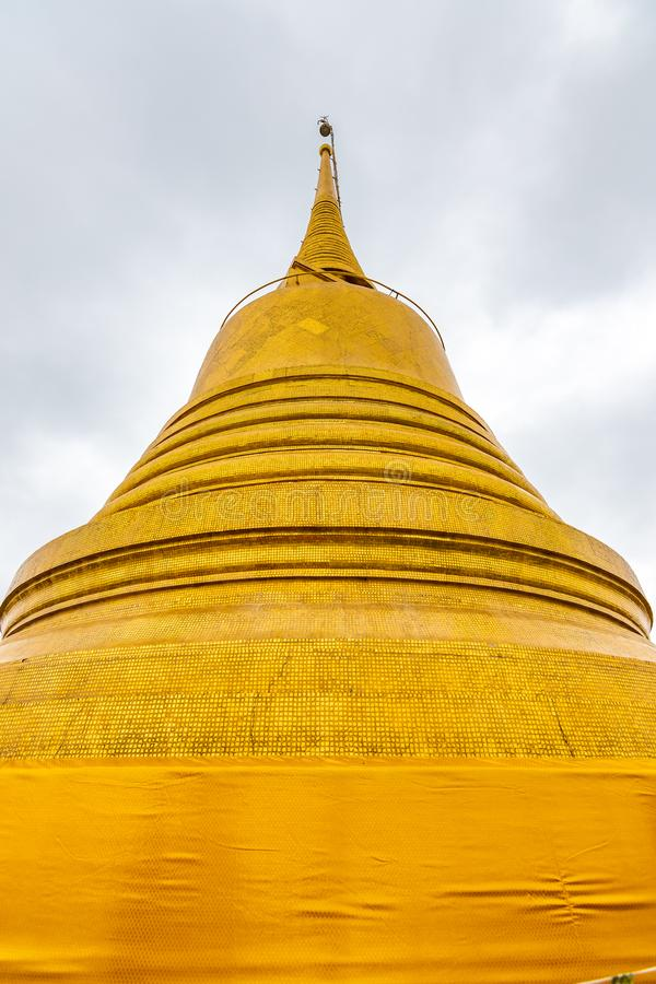 Wat Saket temple with golden stupa and angel statue. Symbol of buddhism in Bangkok city, Thailand. Majestic and religion symbol of. Thai culture. Cloudy weather stock image