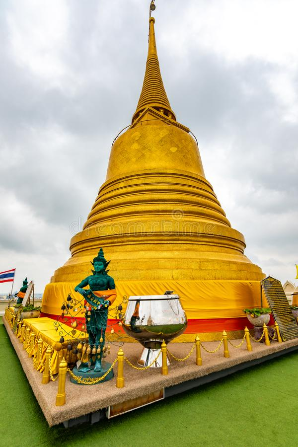 Wat Saket temple with golden stupa and angel statue. Symbol of buddhism in Bangkok city, Thailand. Majestic and religion symbol of. Thai culture. Cloudy weather royalty free stock photography