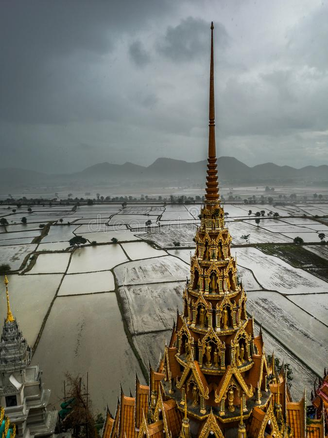 Wat Tham Sua寺庙塔看法有美好的稻田的在水中在背景中在下雨期间 库存图片