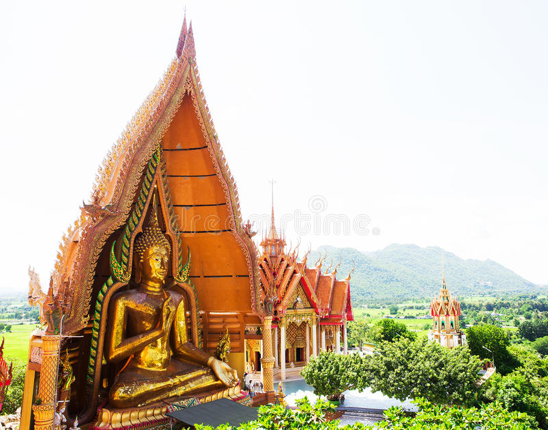 Wat Tham Sua(Tiger Cave Temple), Tha Moung, Kanchanburi, Thailand. A view from the top of the pagoda, golden buddha statue with rice fields and mountain, Wat royalty free stock photography