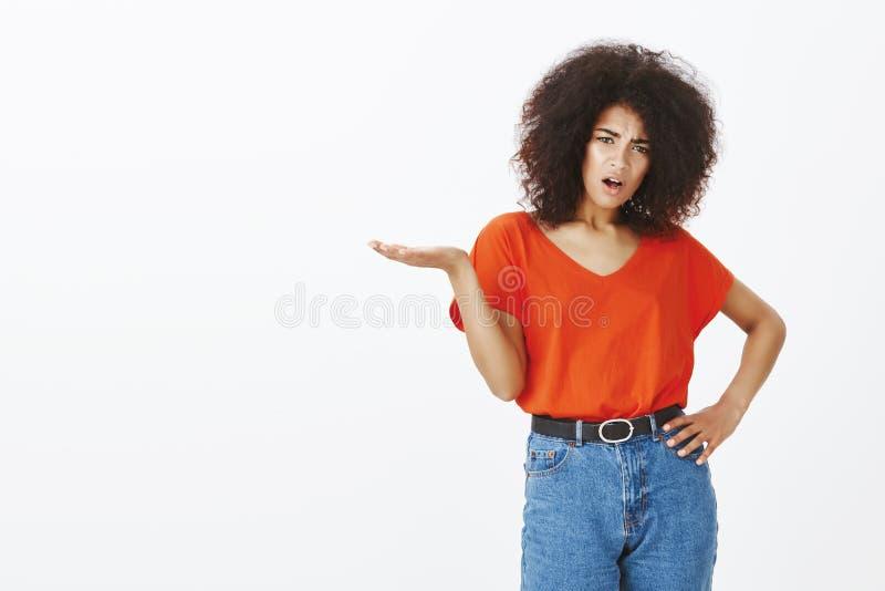 Wat uw punt, mens is Gevraagde teleurgestelde aantrekkelijke donker-gevilde vrouw met afrokapsel, het fronsen, het uitspreiden royalty-vrije stock foto's