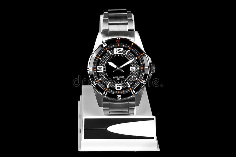 Watch. Elegant watch sitting in support isolated on black background stock images
