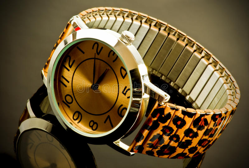 Watch with animal print strap. Closeup of ladies watch with animal print strap reflecting on dark background stock photography