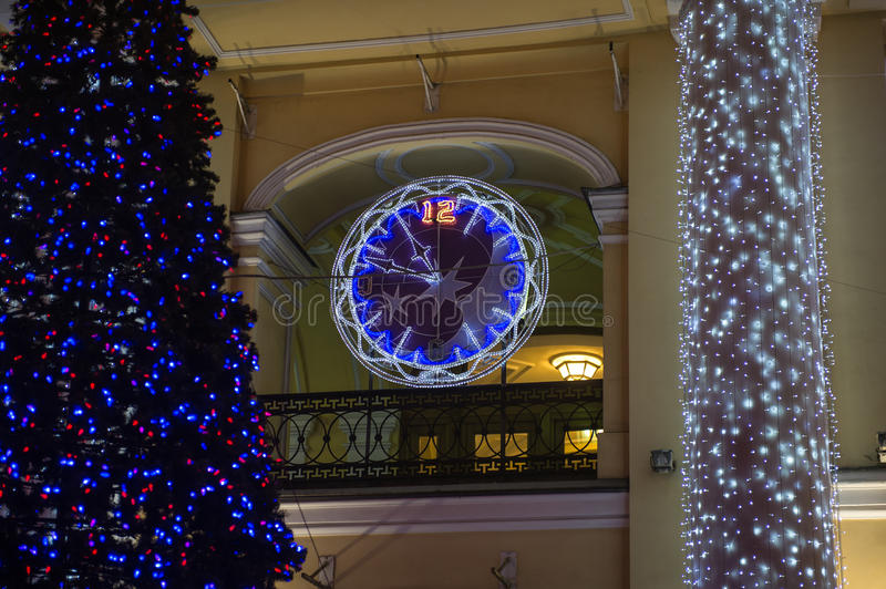 Watch the arrow keys and the dial of the LEDs. Decorated with multicolored diodes for Christmas clock on the wall of a building stock photos
