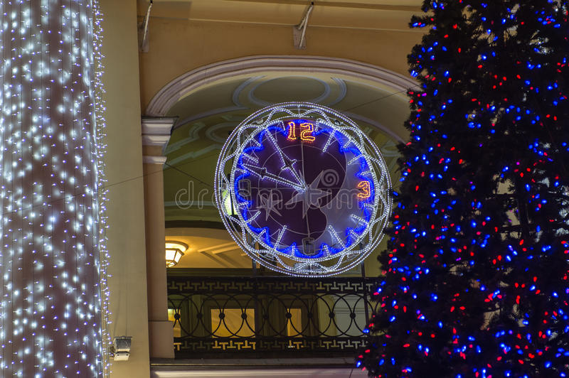 Watch the arrow keys and the dial of the LEDs. Decorated with multicolored diodes for Christmas clock on the wall of a building royalty free stock images