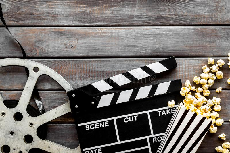 Watch film in cinema with popcorn, video tape and clapperboard on wooden background top view royalty free stock images
