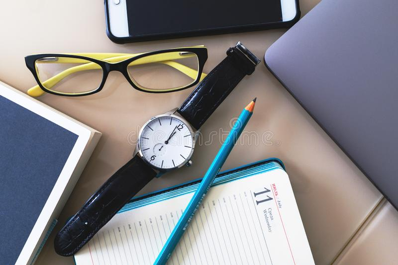Watch, glasses, phone, laptop, notebook and pencil are on the table royalty free stock photography