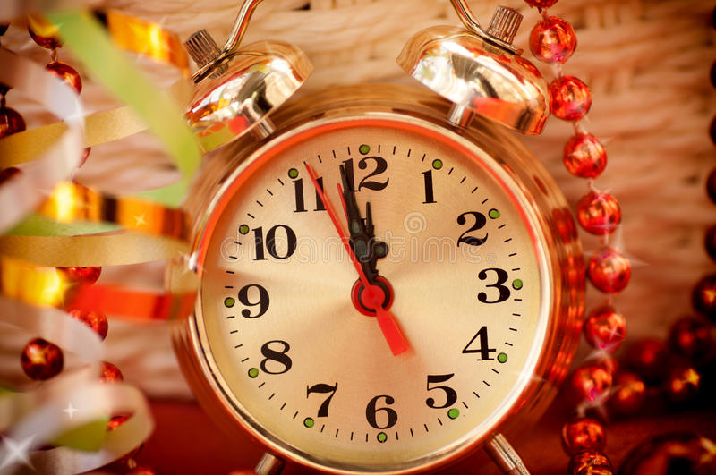 Watch hands by 12 hours and Christmas toys. Background closeup royalty free stock photography