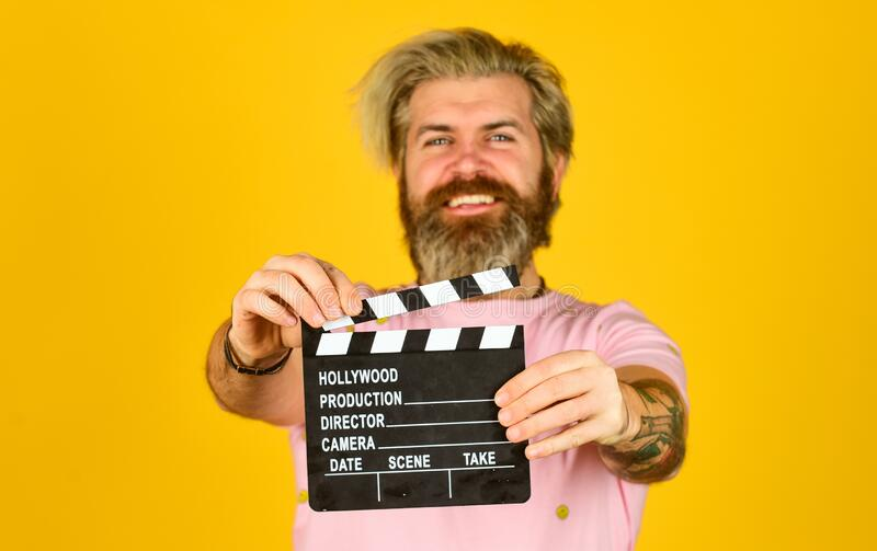 Watch movie. Film director. Actor casting. Shooting scene. Favorite series. Cinema production. Creative producer. Bearded man hold movie clapper. Film maker stock photography