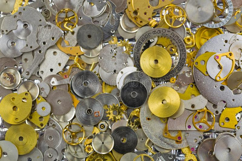 Watch parts in silver golden colors. Small pieces of gears to make charm or DIY jewelry project royalty free stock image