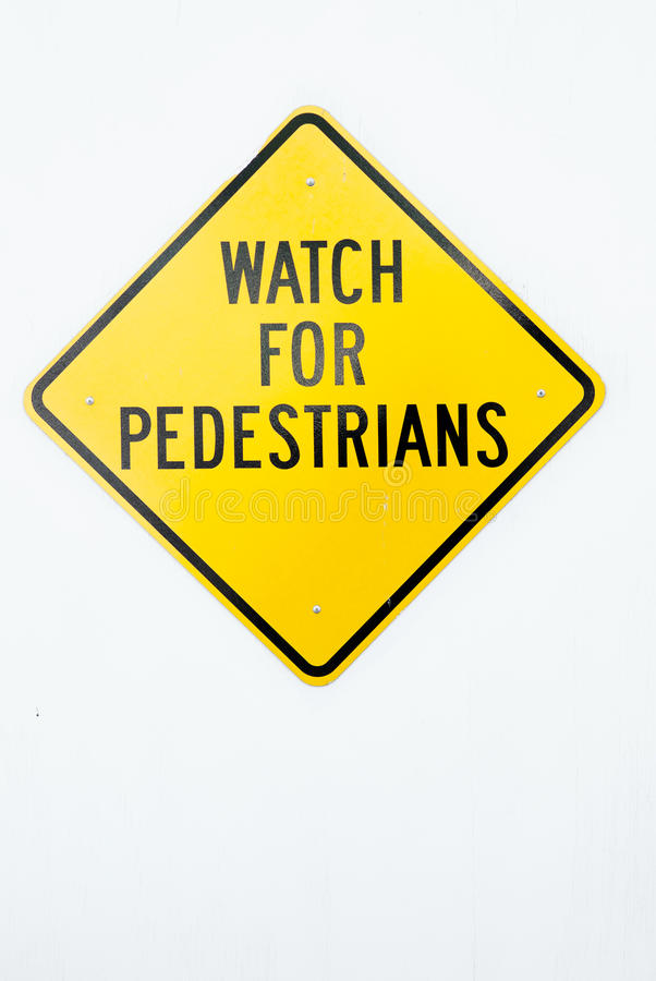 Watch for pedestrians sign. Watch for pedestrians big yellow sign on a white wall royalty free stock image