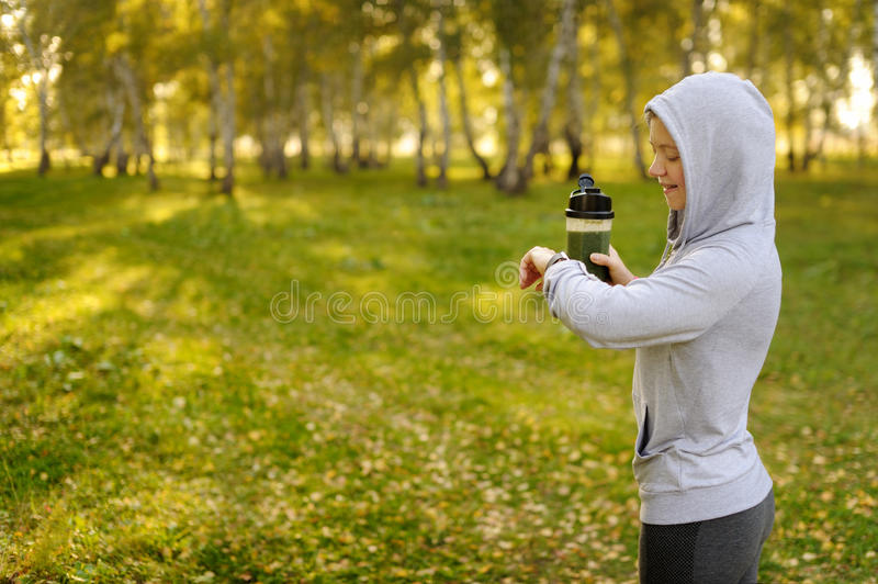 Watch for sports with smartwatch. Jogging training for marathon. Green detox smoothie royalty free stock photography