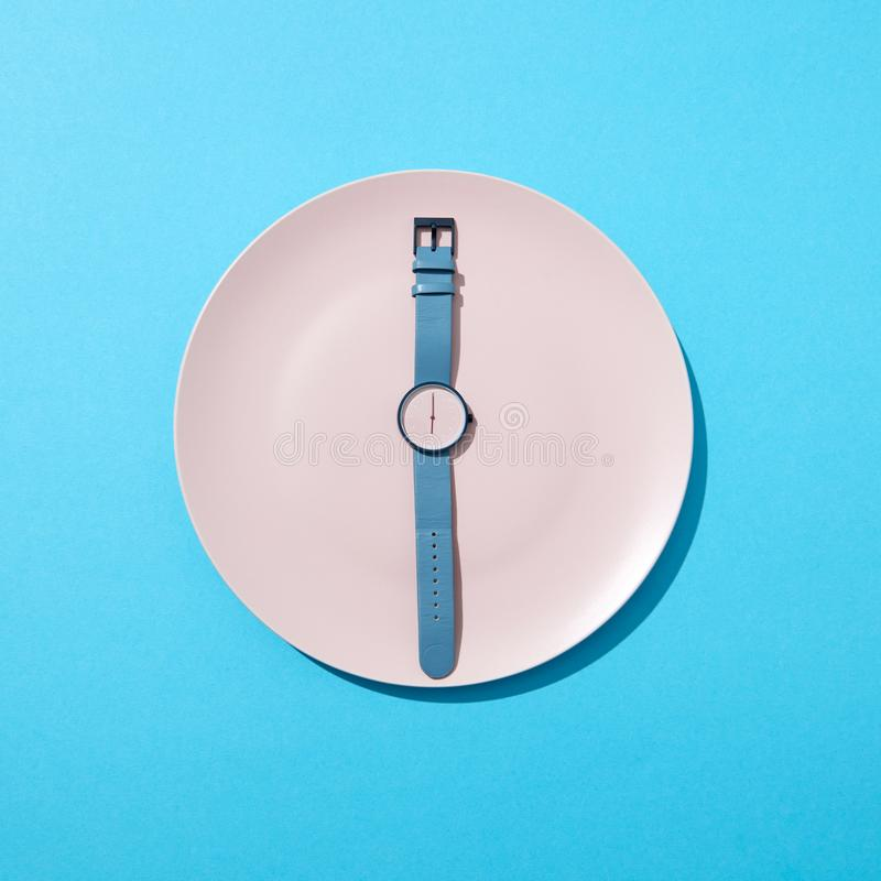 Watch with time six o`clock on a white plate on a blue background. Concept of limiting the intake of food diet and stock photography