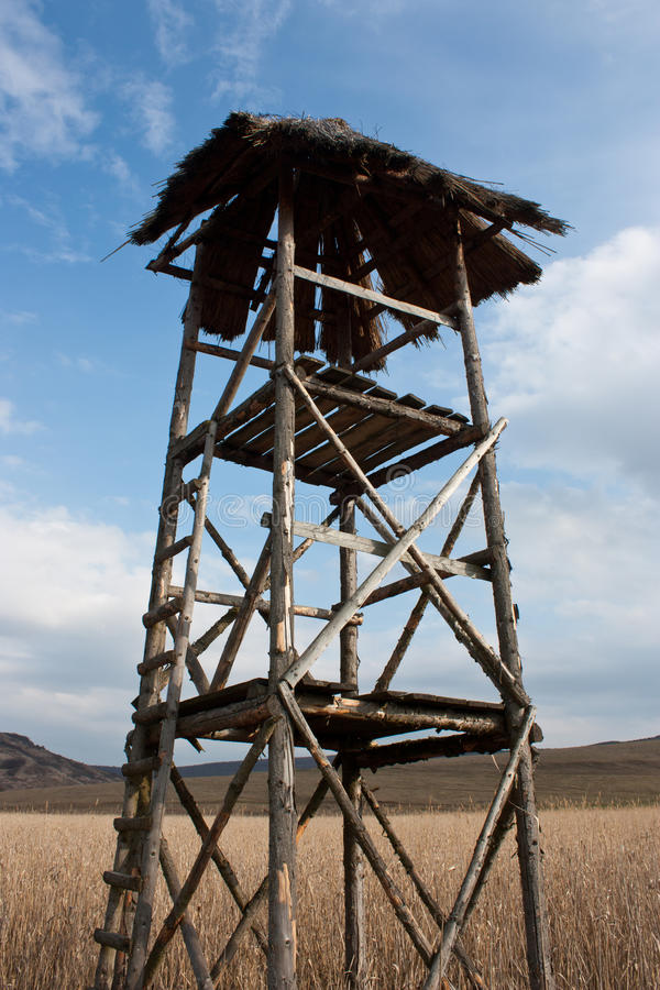 Watch tower. Old wooden watch tower in a field stubble with blue sky background stock images