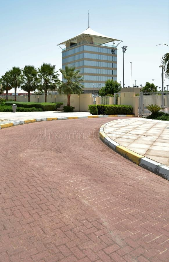 Watch Tower Building, Curved Road to Gate. Paved Parking Area with trees in a line, yellow and white marking on the kerb alongside road going to the gate stock photography