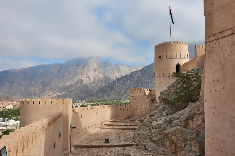 Watch tower of a fort. Watch tower of an ancient fort in oman against the backdrop of a blue sky stock images