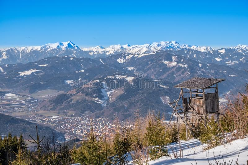 Watch tower view over town Bruck to mountains Goesseck, Reichenstein. Watch tower on snowy mountain Rennfeld view over valley Muerztal with town Bruck an der Mur royalty free stock photos