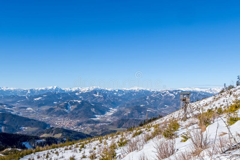 Watch tower view over town Bruck mountains Goesseck, Reichenstein, Hochturm. Watch tower on snowy mountain Rennfeld view over valley Muerztal with town Bruck an royalty free stock image