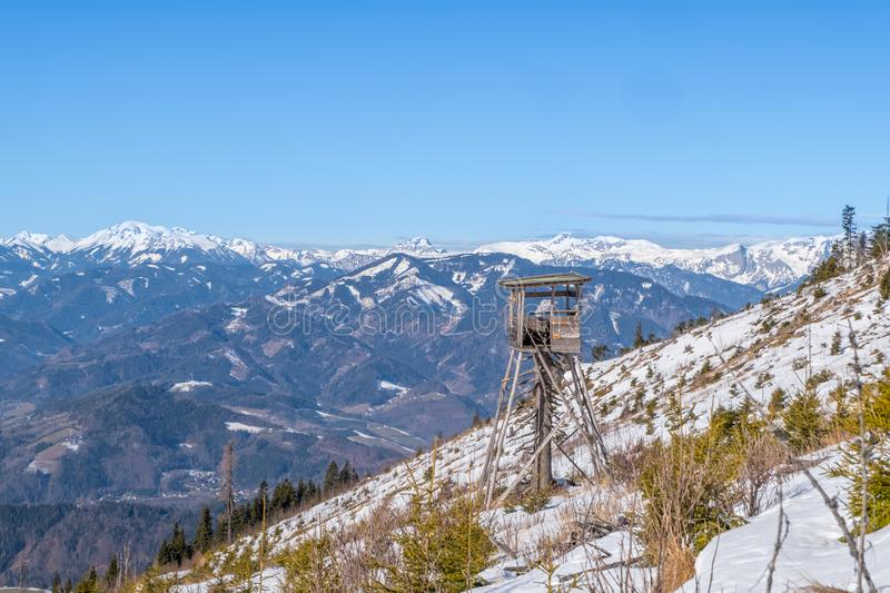 Watch tower view to snowy mountains Hochturm, Brandstein and Hochschwab. Watch tower on snowy mountain Rennfeld view over valley Muerztal to mountains Hochturm royalty free stock photography