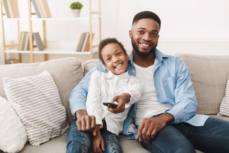 Watch Tv Together. Father And Daughter Switch Channels royalty free stock photography