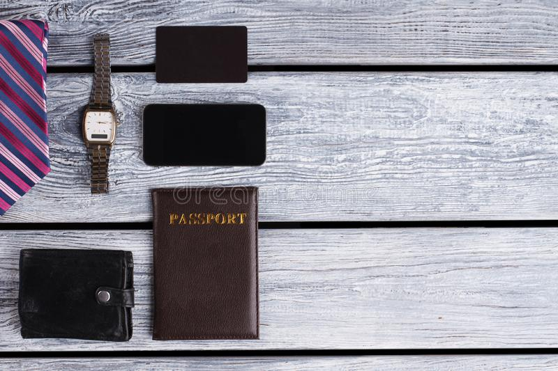 Watch, wallet and passport. Personal men`s stuff in restrained tones. Cellphone and visit card royalty free stock image
