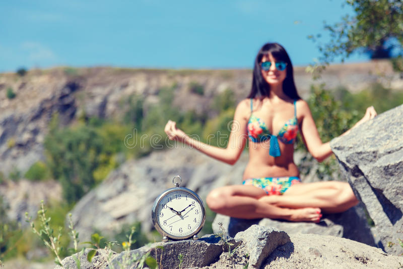 Watches and blurred girl sitting in the lotus position. In the mountains on sunny summer day royalty free stock photo