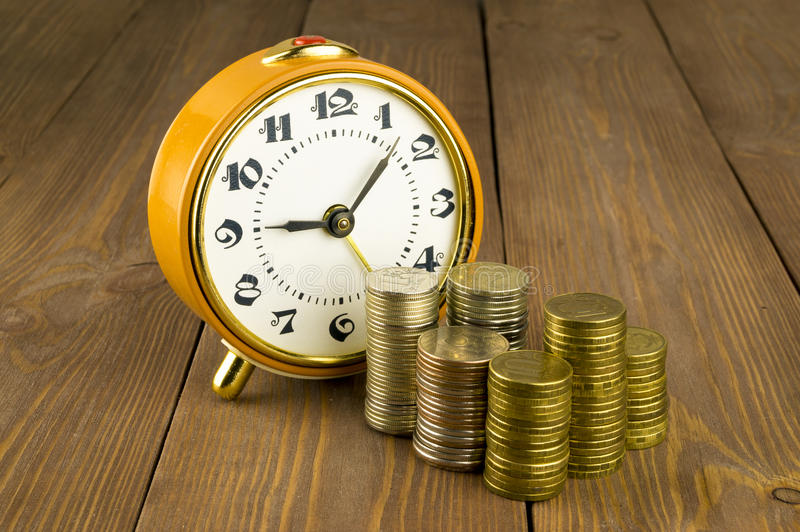 Watches and coins on a wooden table. Yellow watches and coins on a wooden table stock image