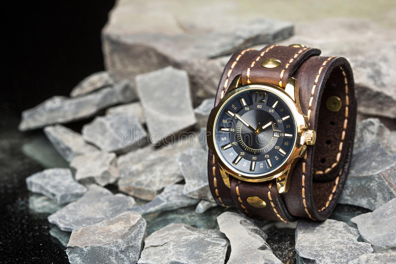 Watches and leather bracelet. Beautiful unusual watches and leather bracelet on the rocks stock photography