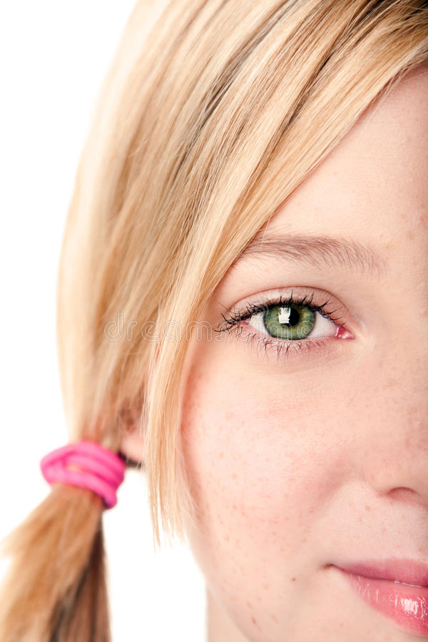 Watchful eye - half face. Beautiful green watchful eye of a teenage girl with blond hair pigtail, isolated stock images