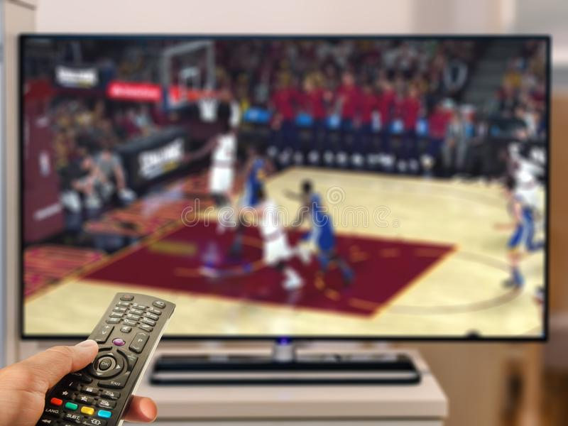 Watching basketball game on TV. At home tv room with remote control royalty free stock photos