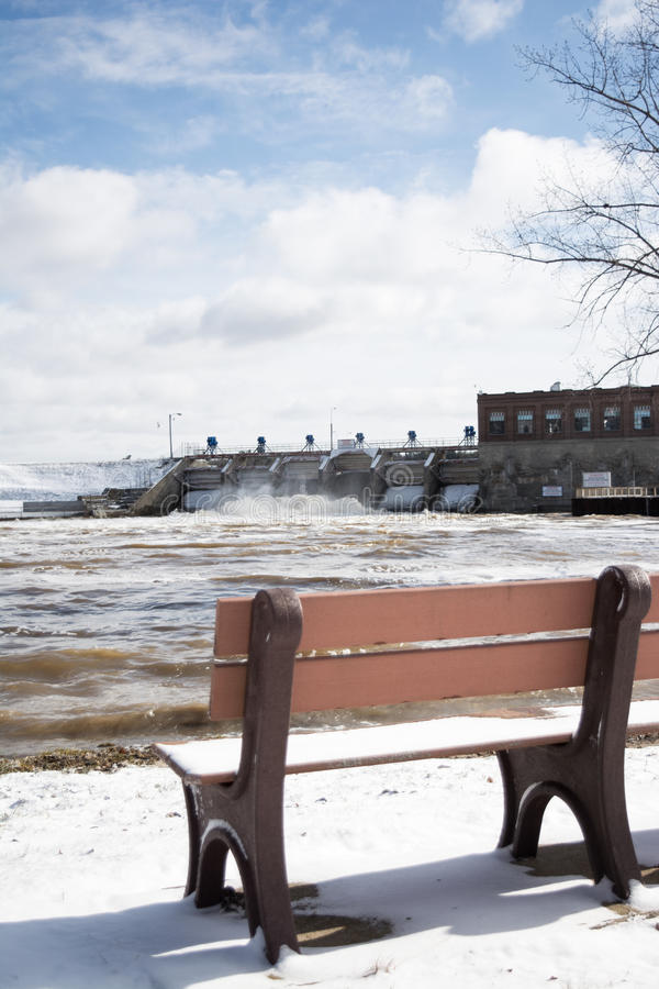 Watching the flood. Bench overlooking a dam with spillway open flooding river stock photography