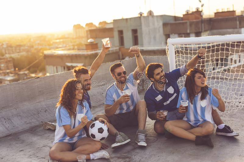 Watching football and drinking beer. Young friends watching a football match, cheerfing for their team and drinking beer on a building rooftop, with cityscape in stock photos