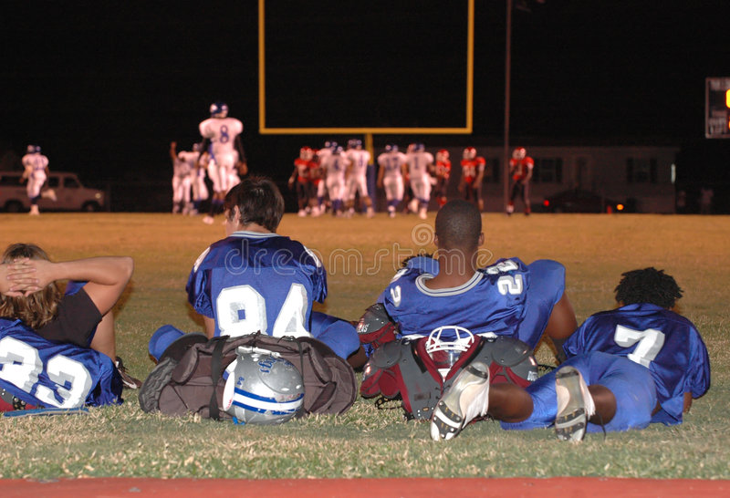 Watching football game. A group of uniformed football players sitting behind end zone watching a football game stock photos