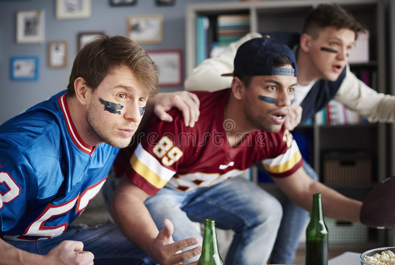 Watching football game. Front view of excited men watching sports game stock images