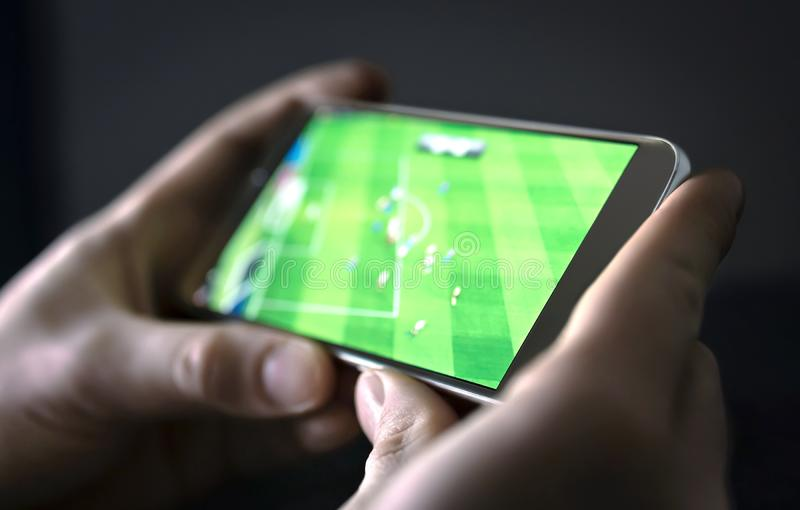 Watching football and sport stream with mobile phone. Man streaming soccer game live, video replay or highlights online. Watching football and sport stream with royalty free stock photos