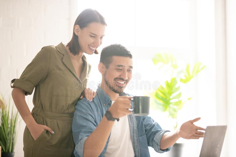 Watching funny video. Young cheerful female in casualwear looking at something funny on laptop display while her husband pointing at it royalty free stock photography