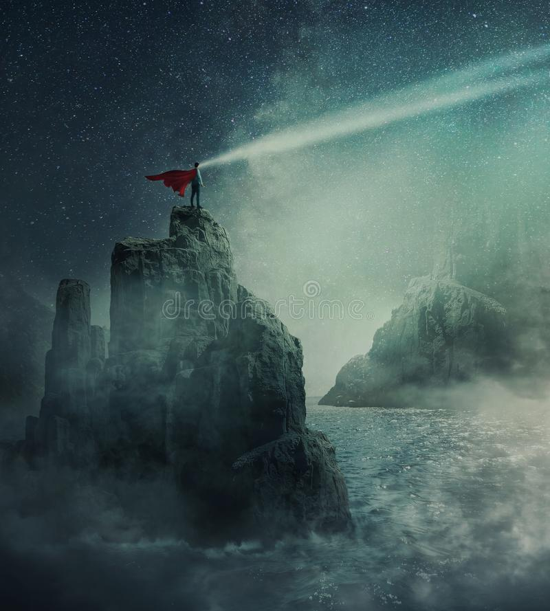 Watching the galaxy. Surreal view as superhero with red cape standing on the top of a cliff surrounded by the sea water watching the starry night sky. Mystical royalty free stock photo