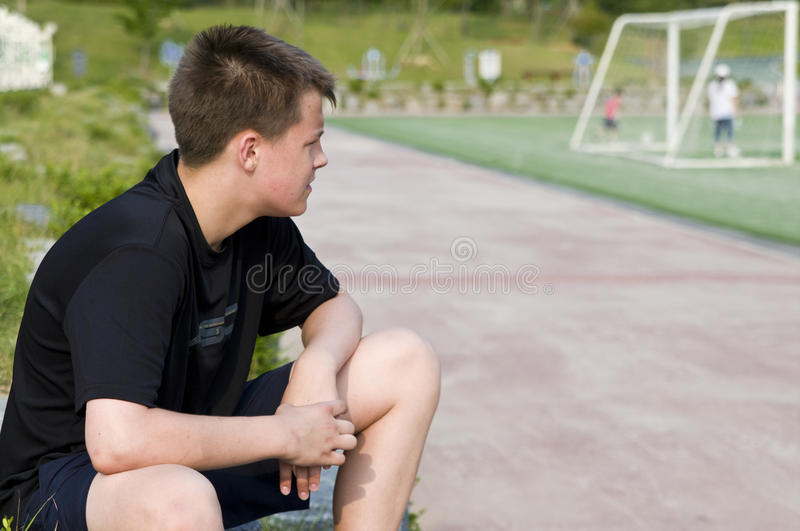 Watching the game. Teenage boy watching outdoor soccer game stock images