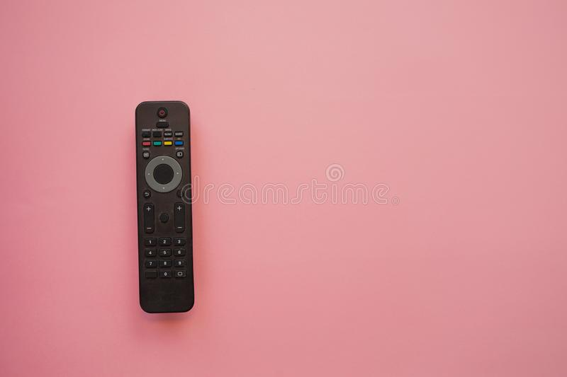 Watching a movie at home, concept on a pink background, copy the space to the right. TV remote royalty free stock images