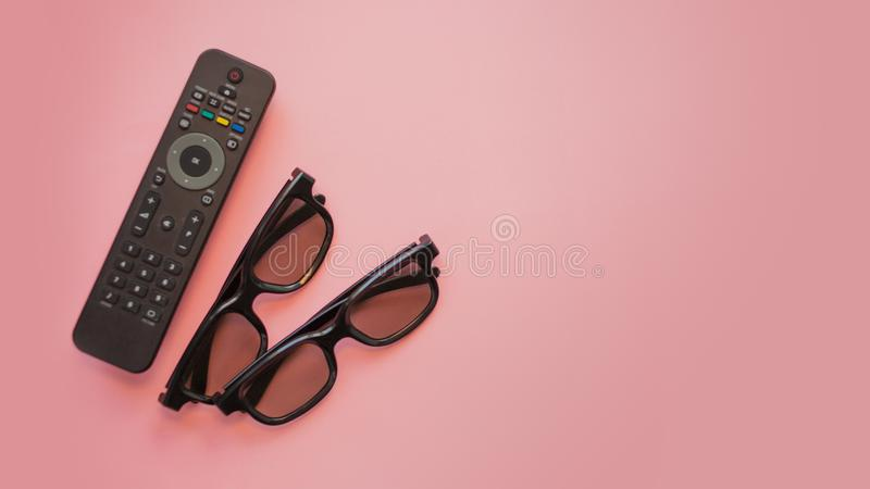 Watching a movie at home, concept on a pink background, copy the space to the right. TV remote and 3D glasses royalty free stock images